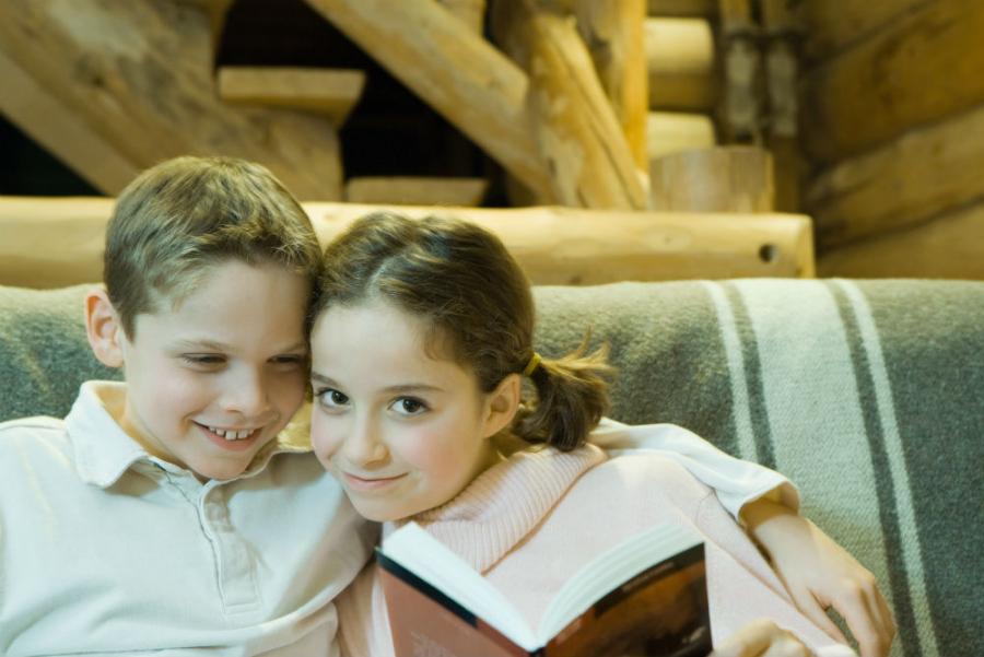 Dreng og pige sidder i sofa med en bog