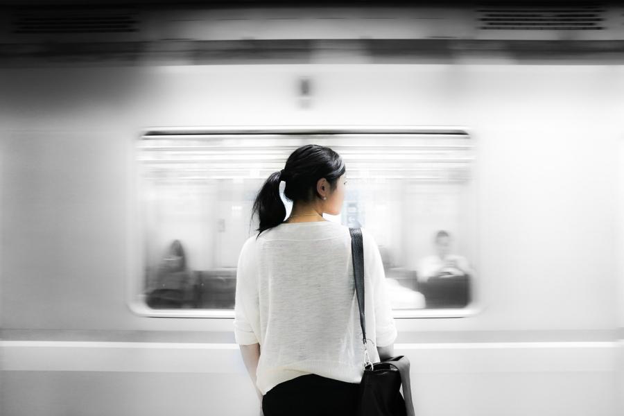 Kvinde står på perron og ser på gennemkørende tog