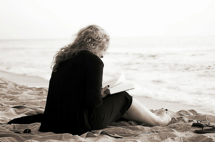 Kvinde læser på strand