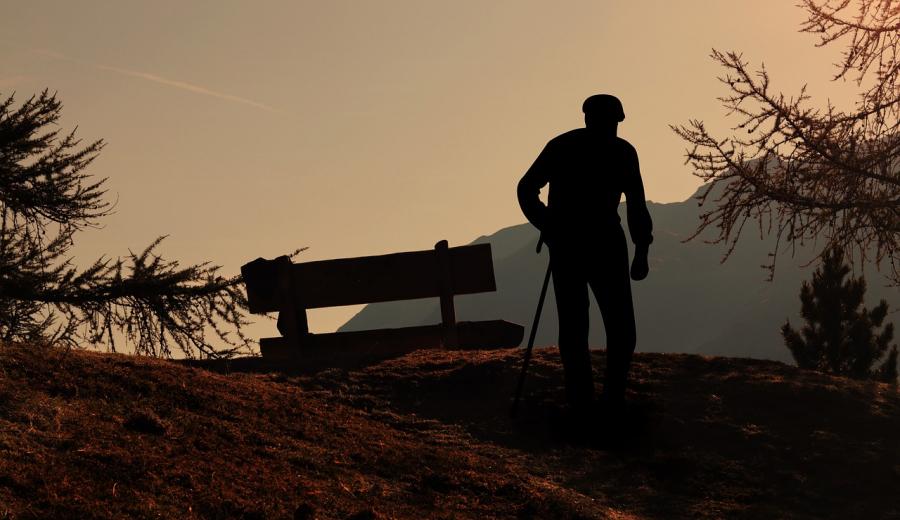 Ældre mand ses i silhouet mod et bjerglandskab