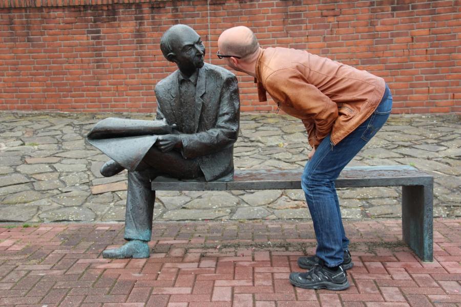 En mand kigger på en bronzeskulptur