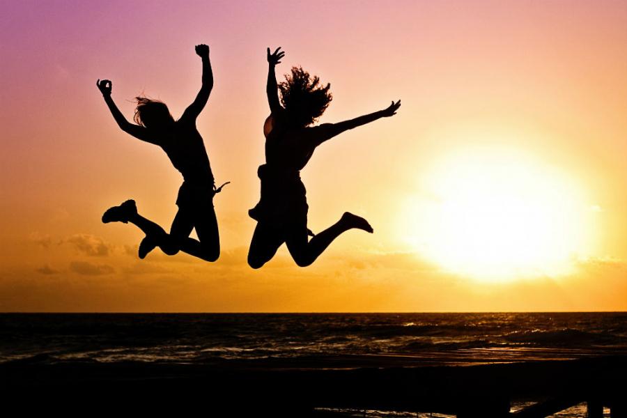 Unge mennesker hopper i luften i solnedgangen ved en strand